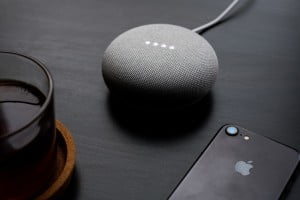 google home mini on a table with iPhone 7