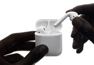 Wirelessly charged Apple AirPods in hands of a person