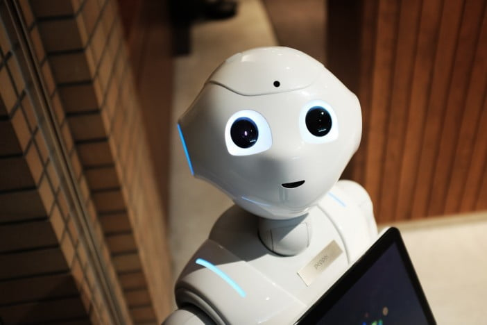 A robot looking at the camera while holding a tablet computer