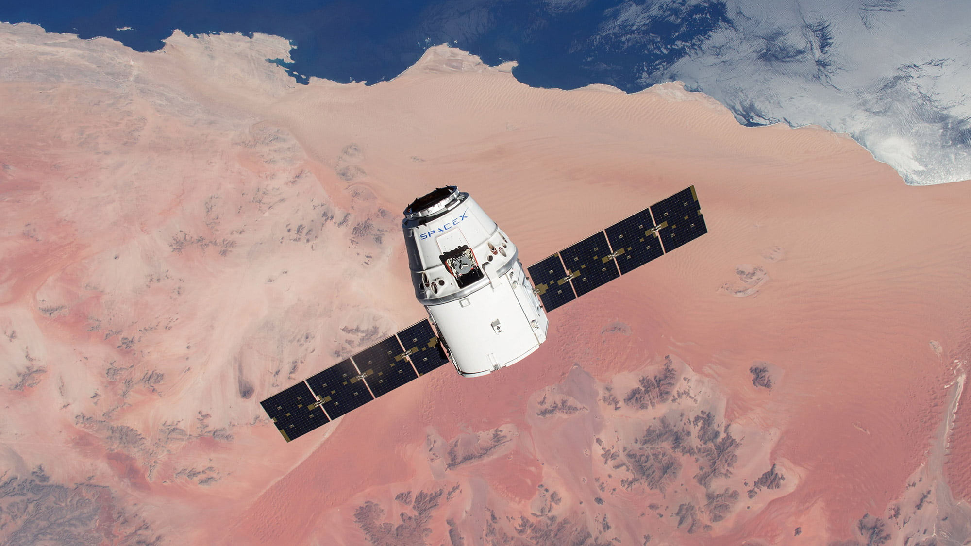 A picture of SpaceX's Dragon spacecraft with solar arrays deployed carrying cargo to the International Space Station (ISS) for NASA.