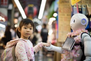 A photo of a child shaking hand with a robot