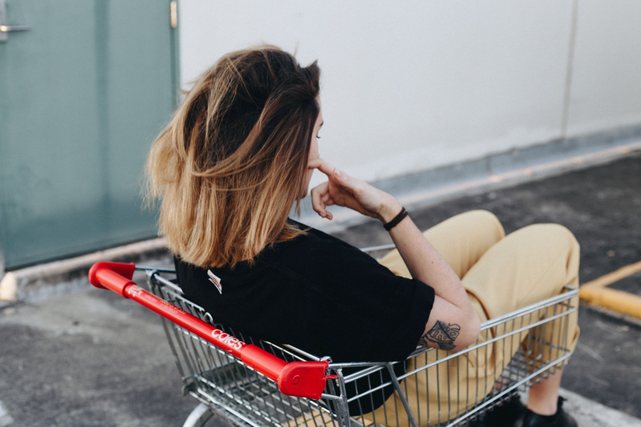 A photo of a girl sitting in a shopping cart