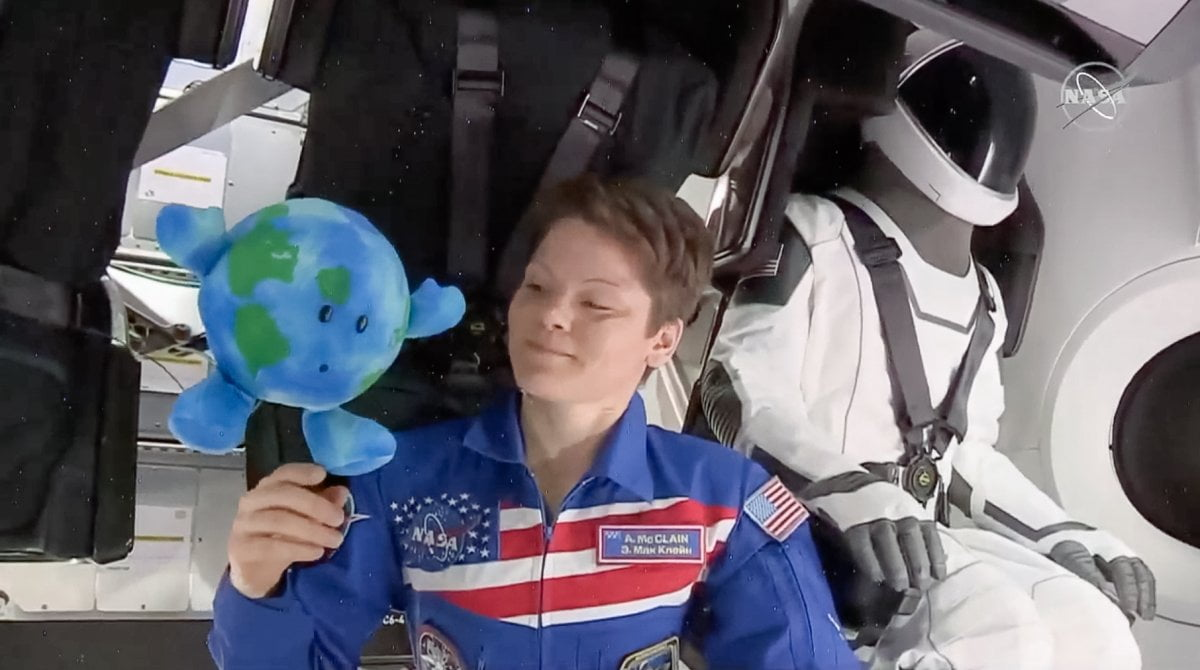 A photo of Woman in space with SpaceX's special suite and a toy earth
