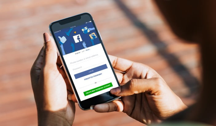 A photo of iPhone X in hands of a female with Facebook login screen open