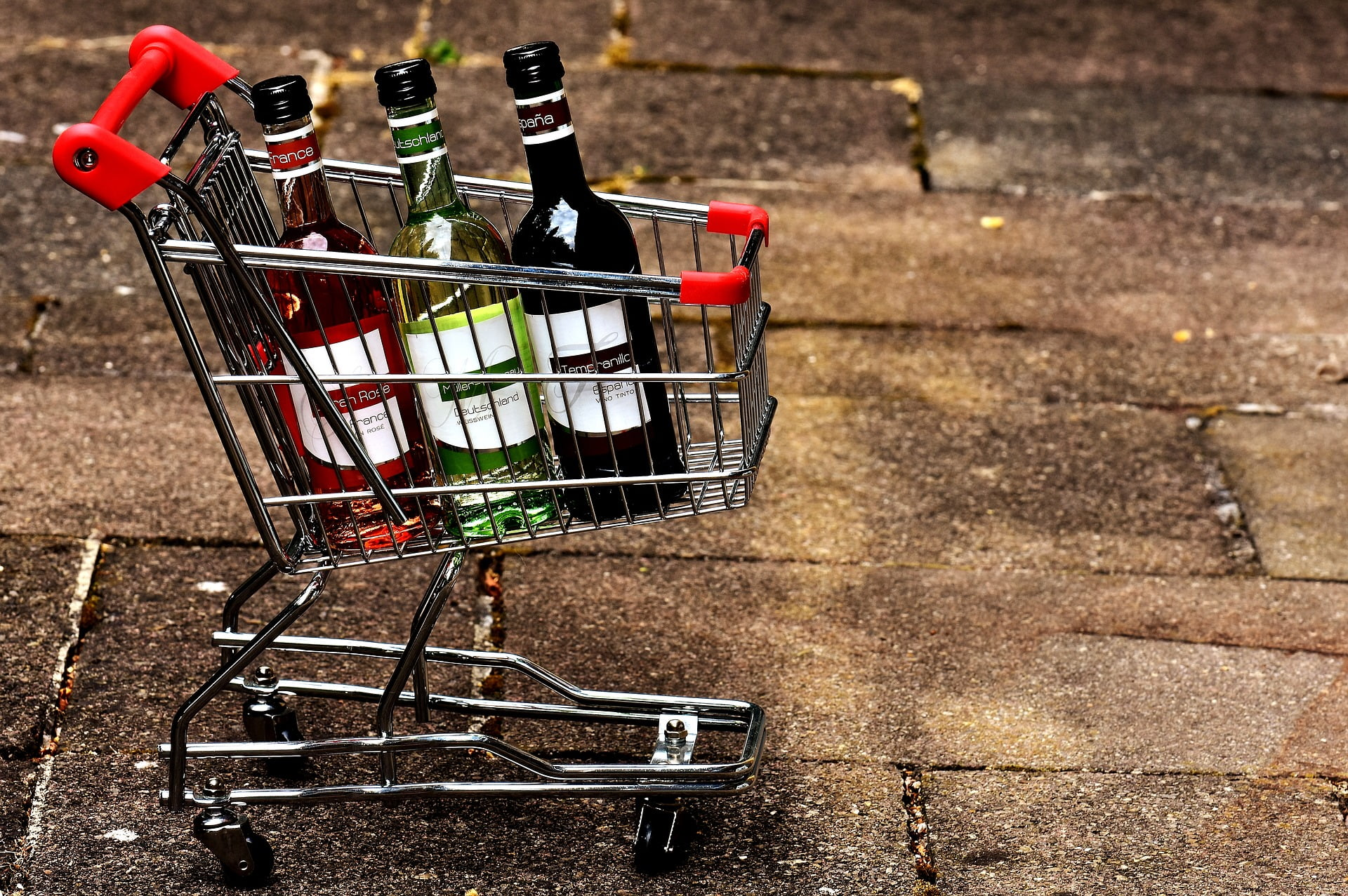 A photo of shopping cart with three different drinks in it