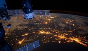 An image of space craft in the space with a stunning view of night lights on earth