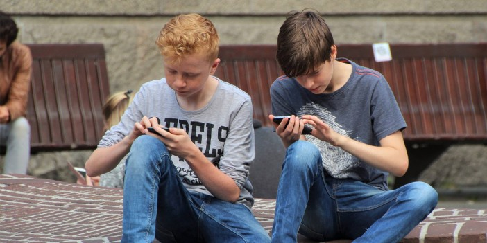 two kids using their phones