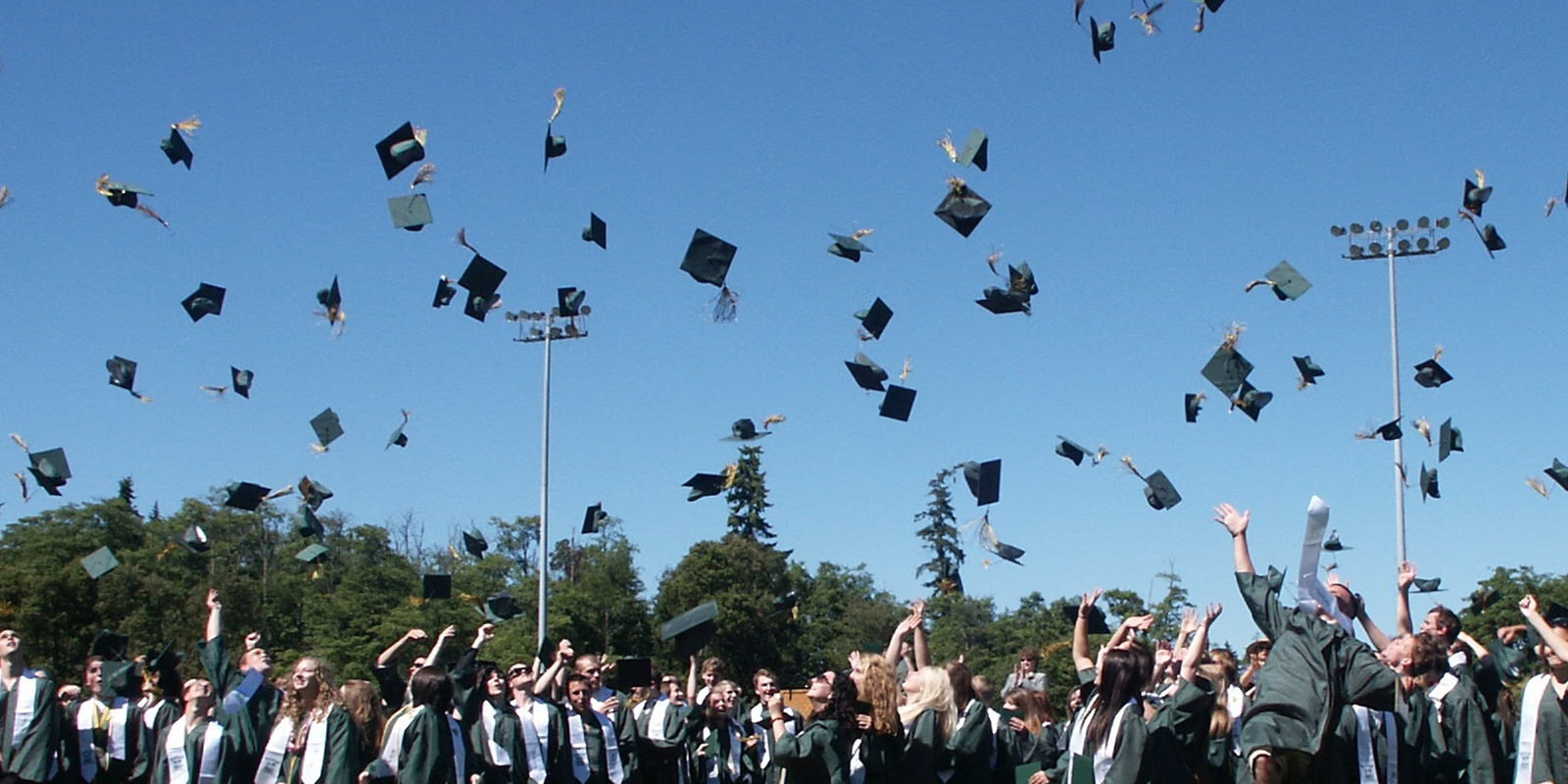 high school students tossing their graduation hats in the air
