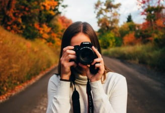 A photo of a girl holding a Canon camera