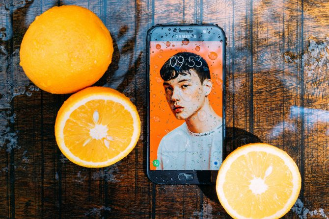 A photo of waterproof smartphone near oranges