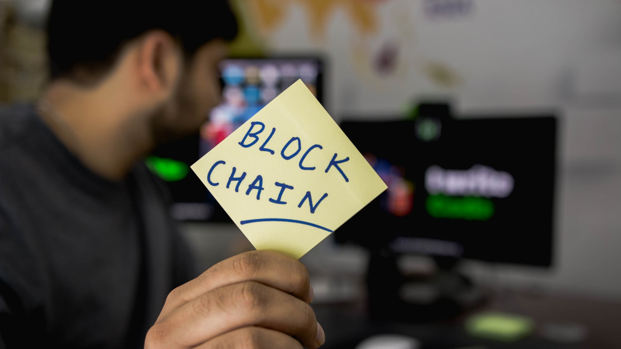 A person showing Blockchain written on a paper