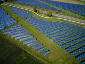 An aerial photo of solar panels on green grass