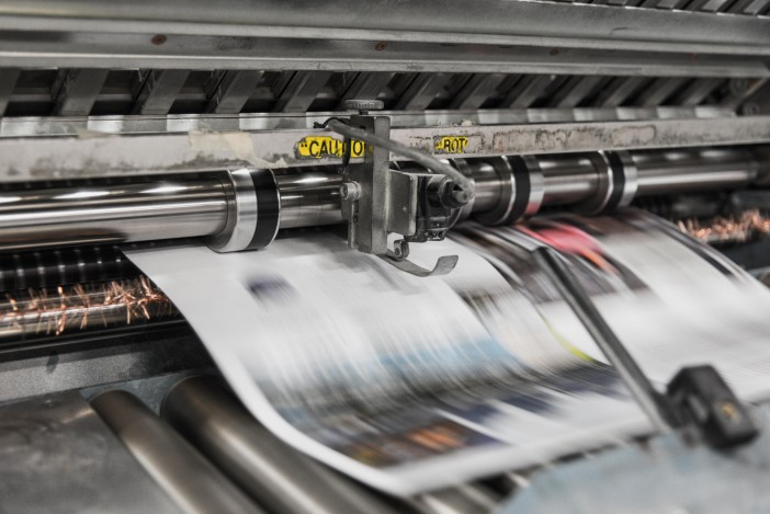 A photo of Newspaper machine printing out Newspapers