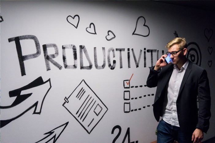 "A photo of a man passing by sign of ""Productivity"" while talking on phone"