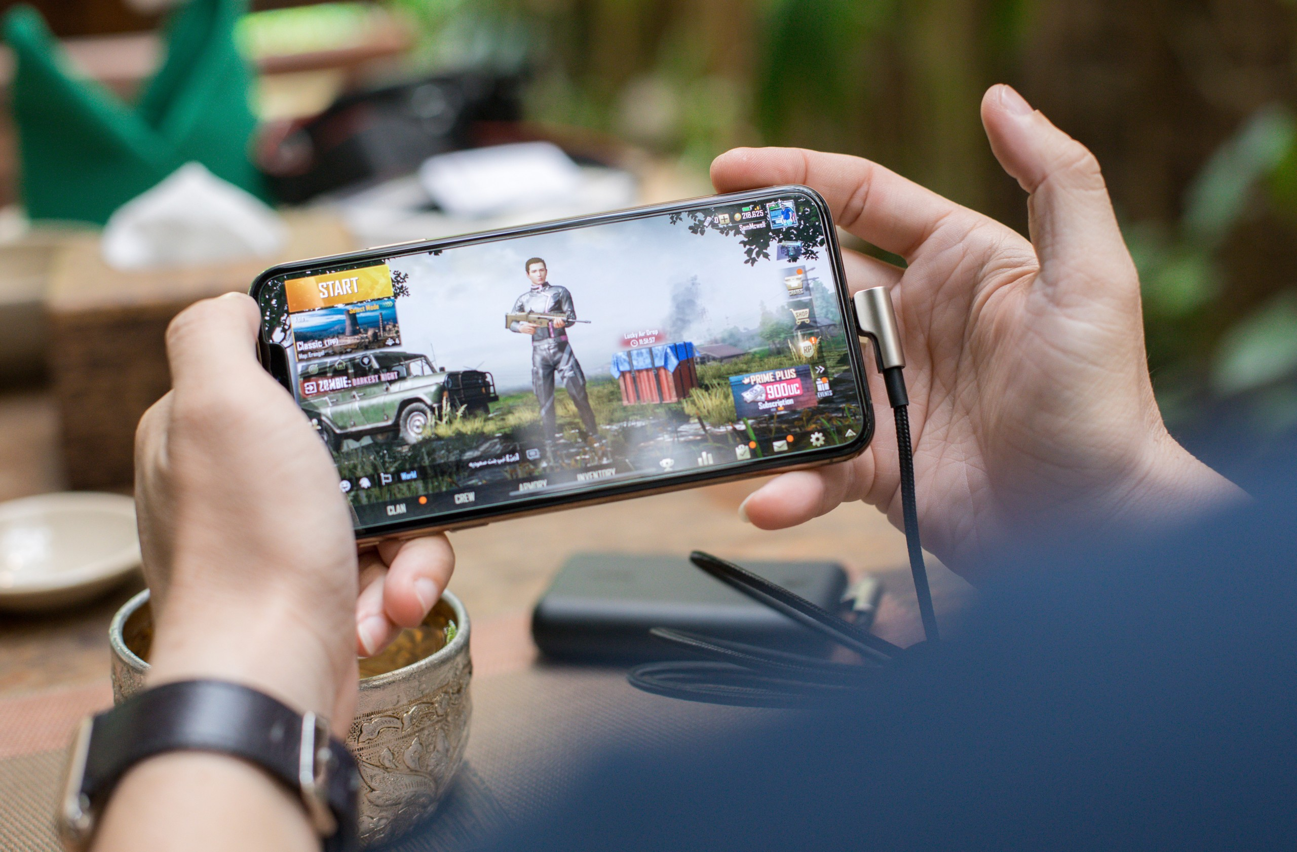 A photo of a person playing PUBG on mobile phone