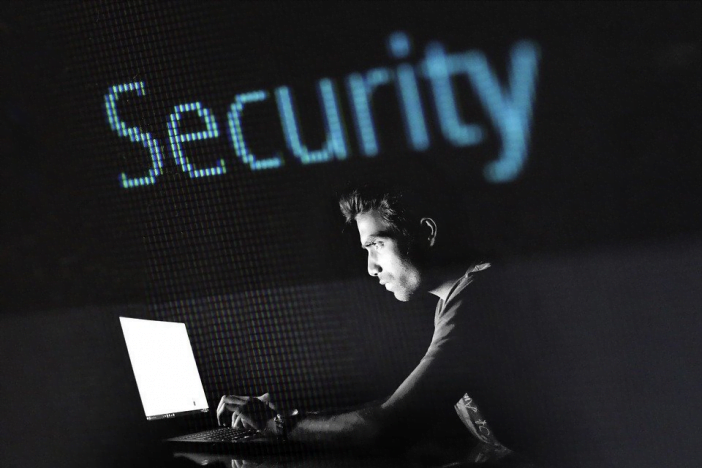 A photo of a person using laptop for security