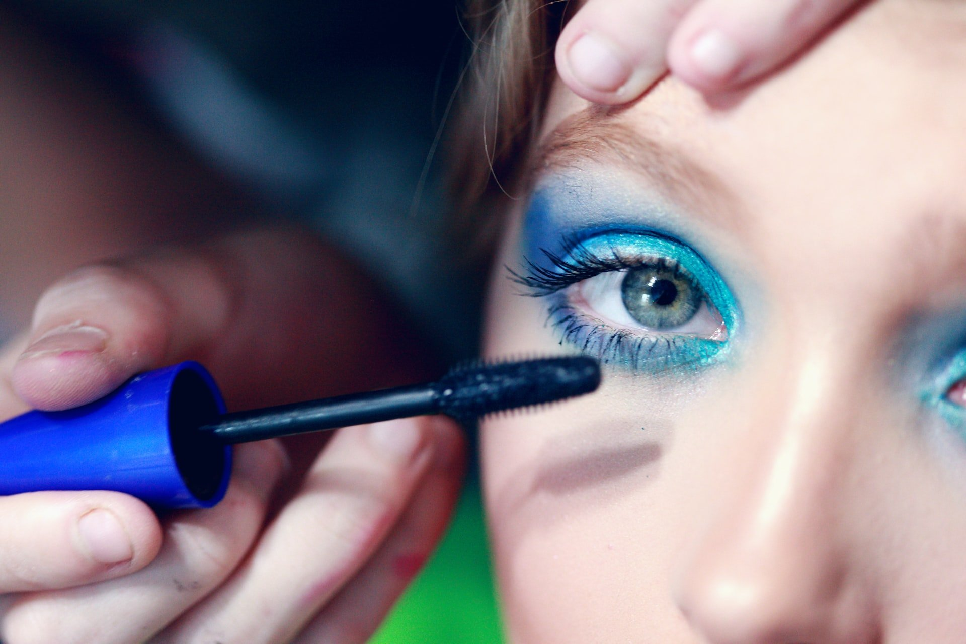 Mascara being applied to a woman's eyelash with blue eyeshadow