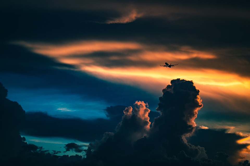 An Airplane passes through clouds during sunset