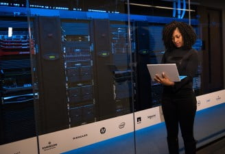 A girl using laptop near servers