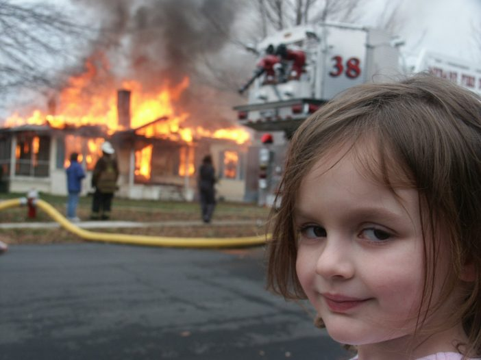 A girl standing alone and the fire in background